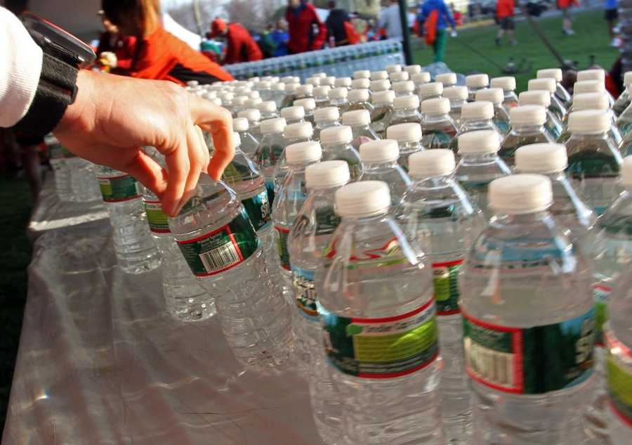 A runner grabs water before the race in Hopkinton.