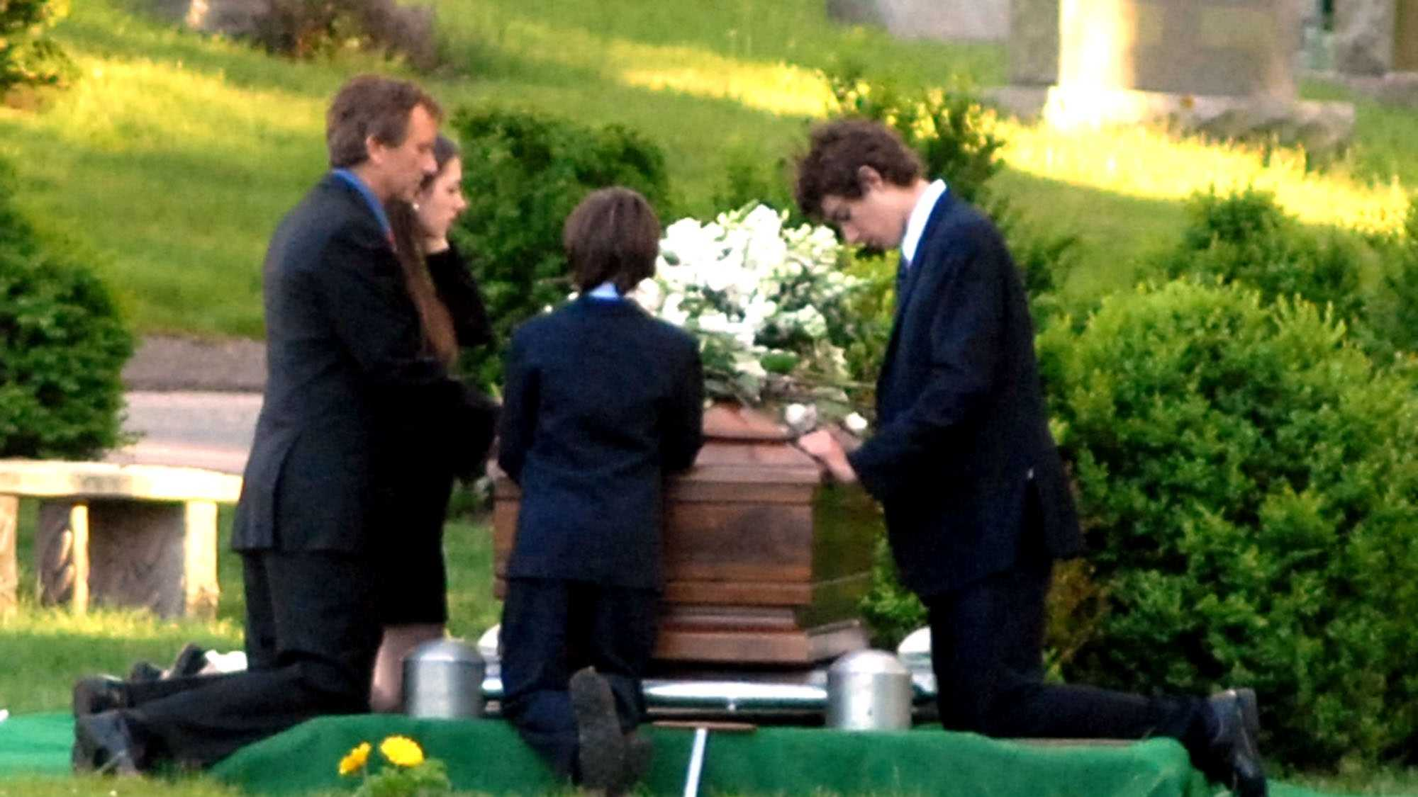 Robert Kennedy, Jr. (left) and his children pray at the casket of the late Mary Kennedy during a burial service at St. Francis Xavier Cemetery in Centerville, Massachusetts Saturday, May 19, 2012.