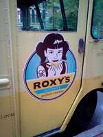 Roxy's logo featuring an emo-esk Wendy munching on a grilled cheese