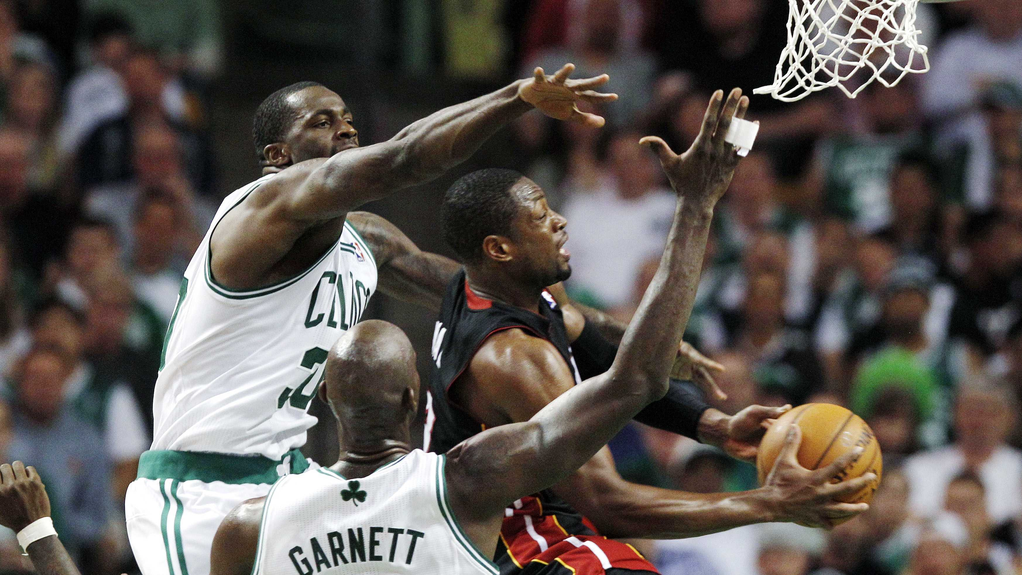 Miami Heat guard Dwyane Wade drives against Boston Celtics forwards Kevin Garnett and Brandon Bass.