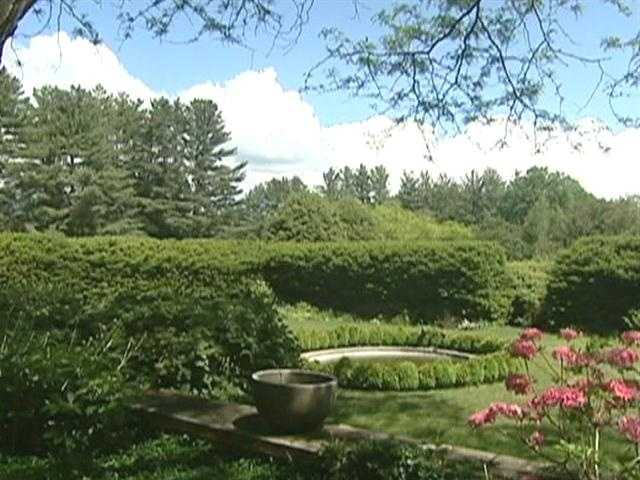 The grounds are landscaped with lovely formal gardens and stone walls.