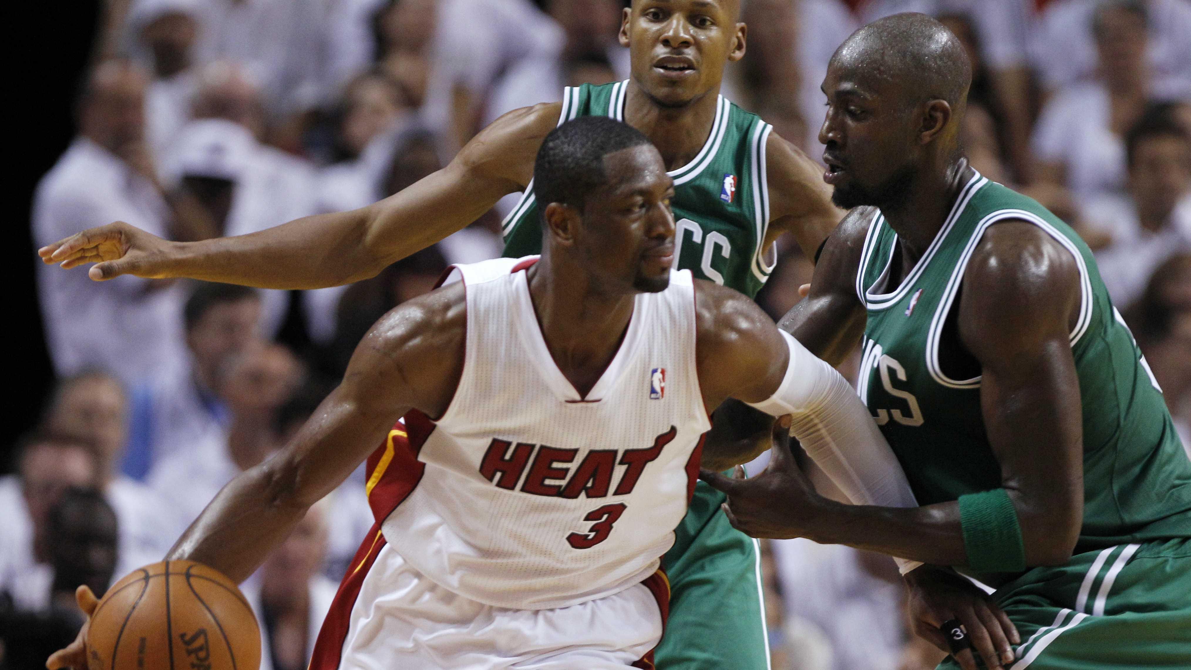 Miami Heat's Dwyane Wade dribbles as Boston Celtics' Kevin Garnett, right, defends.
