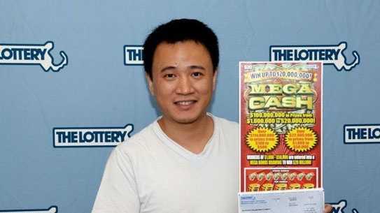 Yu Zhou with his winning Mega Cash scratch ticket.