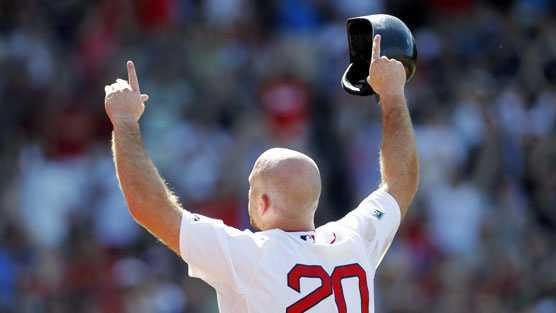 Youkilis raises his arms to the crowd after his last game as a Red Sox.
