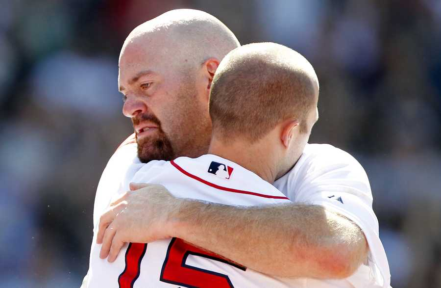Kevin Youkilis, left, hugs teammate Dustin Pedroia as Youklis comes off the field after being traded to the White Sox.