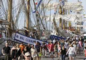 Visitors walk past tall ships on the Fish Pier in Boston. Thousands of sailors aboard at least 18 naval ships from around the world gathered in Boston to mark the 200th anniversary of the War of 1812 and the Star-Spangled Banner.