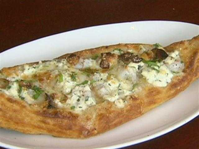 The escargot tart, a very buttery pizza-dough-meets-croissant, is baked in the brick oven.