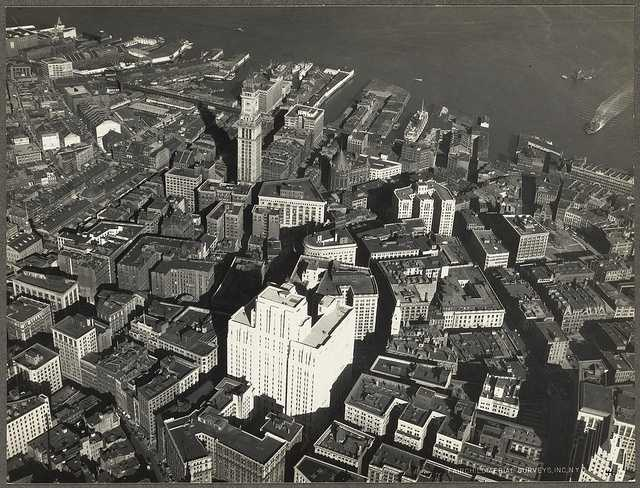 This is an aerial view of what was called the business district in 1932. The old federal courthouse is seen in the foreground, with the Custom House Tower behind it.