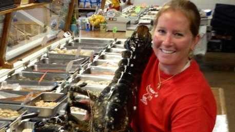 Elise Costa, manager of Captain Elmers Fish Market in Orleans with the 21 pound lobster.