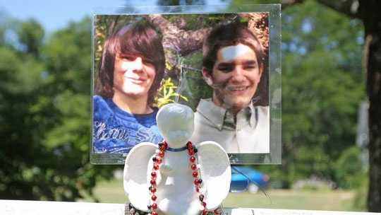 A cross with photographs of Dalton Goulart, 20, is set up at Cedar Street and Plympton Street in Middleborough, where Goulart was stabbed to death in November.
