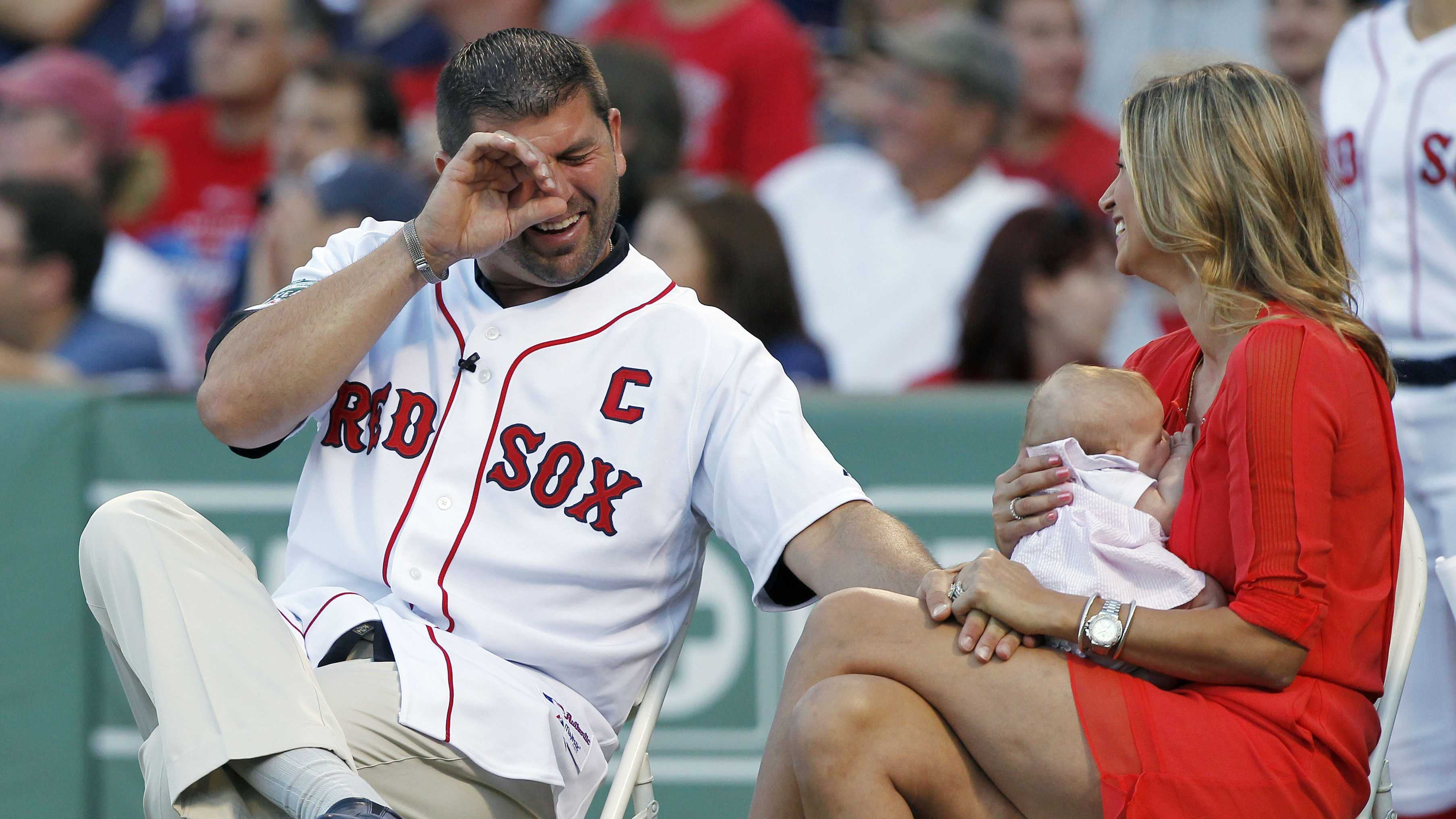Former Boston Red Sox player Jason Varitek, left, reacts next to his wife Catherine and baby daughter Liv during a ceremony to honor his time with the team.