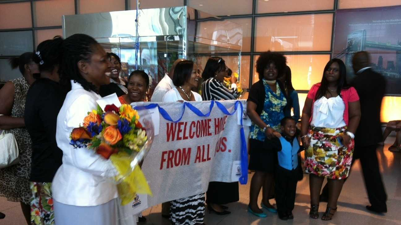 The families of the Rev. Michel Louis and Lissa Alphonse await their arrival home from Egypt at Logan International Airport.