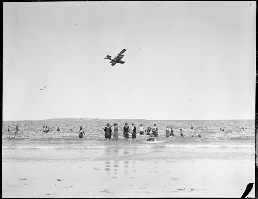 A biplane flies over Revere Beach in this picture taken sometime between 1917 -1934.