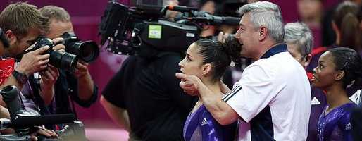 Coach Mihai Brestyan holds the head of U.S. gymnast Alexandra Raisman as he directs her to look at photographers and cameramen, while Gabrielle Douglas is seen at right. Raisman and Douglas have qualified for the women's all-around finals.