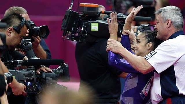 Coach Mihai Brestyan lifts the hands of U.S. gymnast Alexandra Raisman after she qualified for the women's all-around finals during the Artistic Gymnastics women's qualification.
