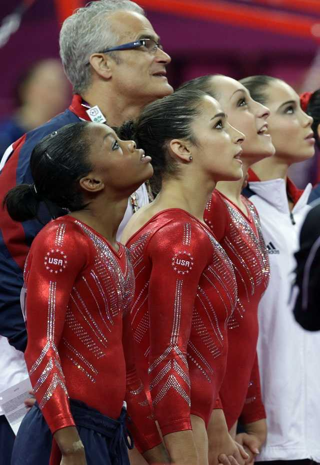 U.S. gymnasts, from left to right, Gabrielle Douglas, Alexandra Raisman, Jordyn Wieber and McKayla Maroney along with U.S. head coach John Geddert, back, watch the screen moments before the results were declared during the Artistic Gymnastic women's team final