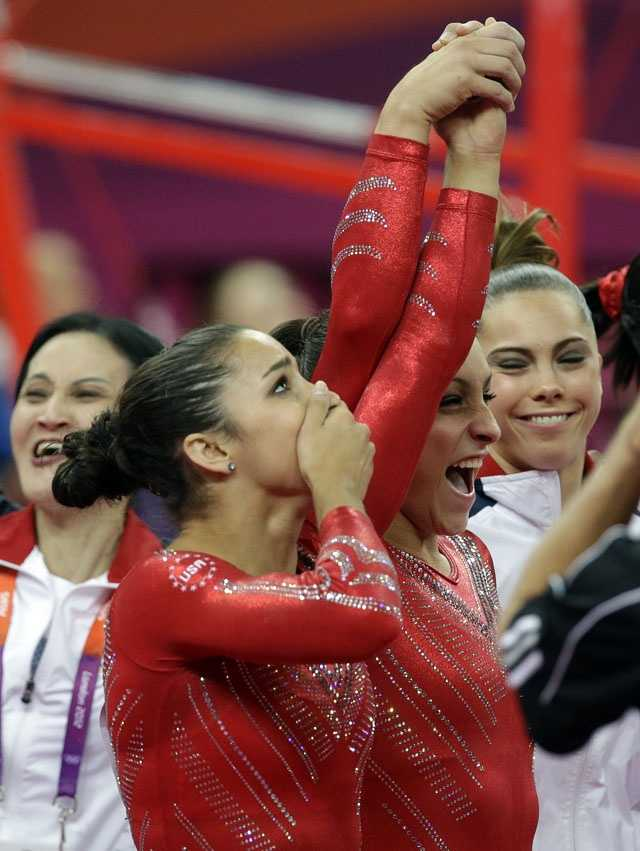 U.S. gymnast Jordyn Wieber, center, lifts up the hand of teammate Alexandra Raisman, as they celebrate along with McKayla Maroney after being declared winners of the gold medal during the Artistic Gymnastic women's team final.