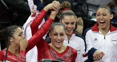 U.S. gymnast Jordyn Wieber, second left, lifts up the hand of teammate Alexandra Raisman, as they celebrate along with McKayla Maroney and Kyla Ross after being declared winners of the gold medal during the Artistic Gymnastic women's team final.