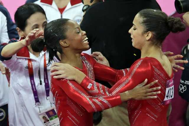 U.S. gymnast Gabrielle Douglas hugs teammate Alexandra Raisman after Raisman's floor exercise during the Artistic Gymnastic women's team final