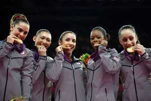 U.S. gymnasts, left to right, McKayla Maroney, Kyla Ross, Alexandra Raisman, Gabrielle Douglas and Jordyn Wieber celebrate during the medal ceremony of the Artistic Gymnastics women's team final.