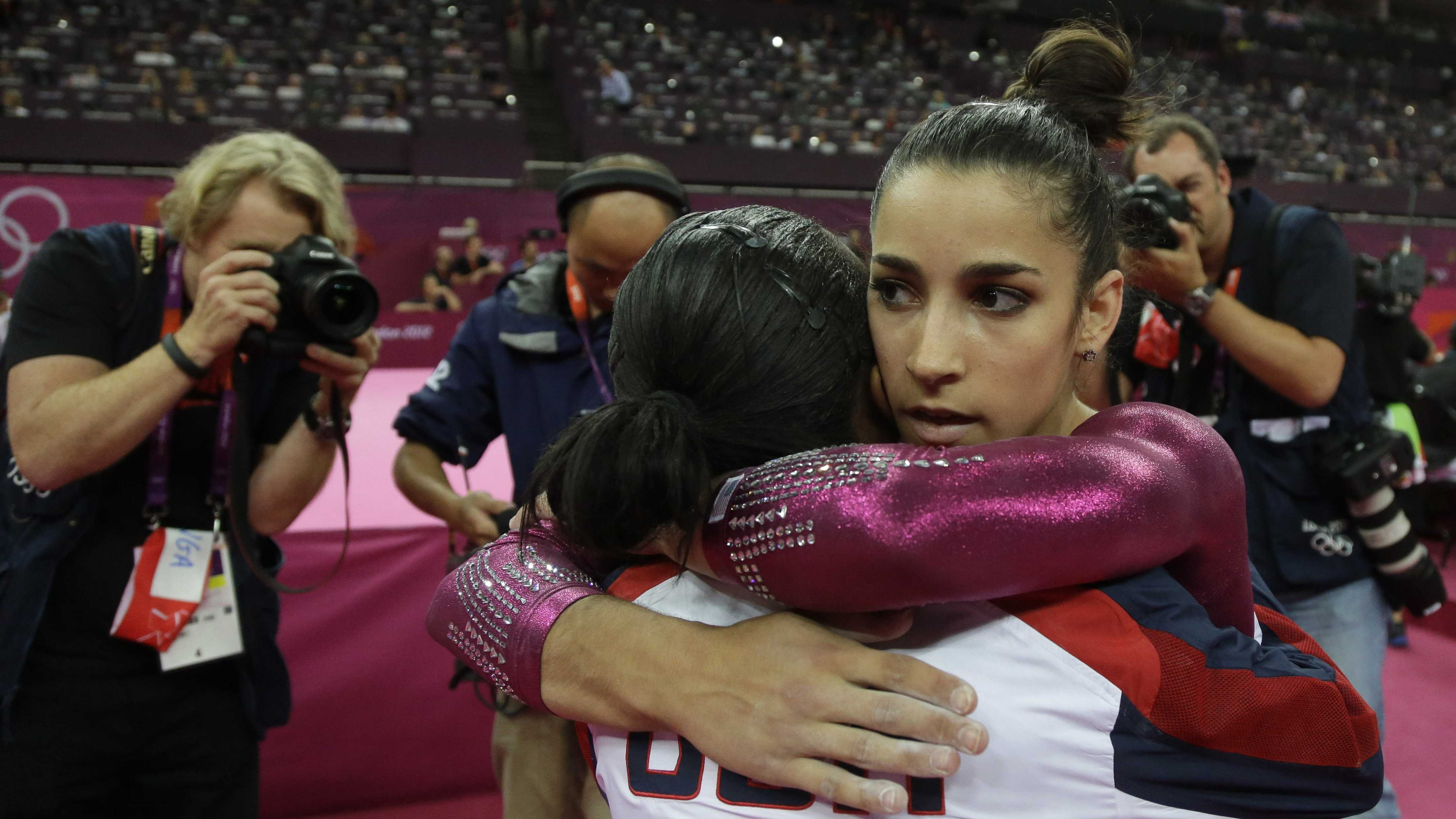 U.S. gymnast Gabrielle Douglas, left, hugs teammate Alexandra Raisman after the latter's performance on the floor during the artistic gymnastics women's individual all-around competition at the 2012 Summer Olympics, Thursday, Aug. 2, 2012, in London.