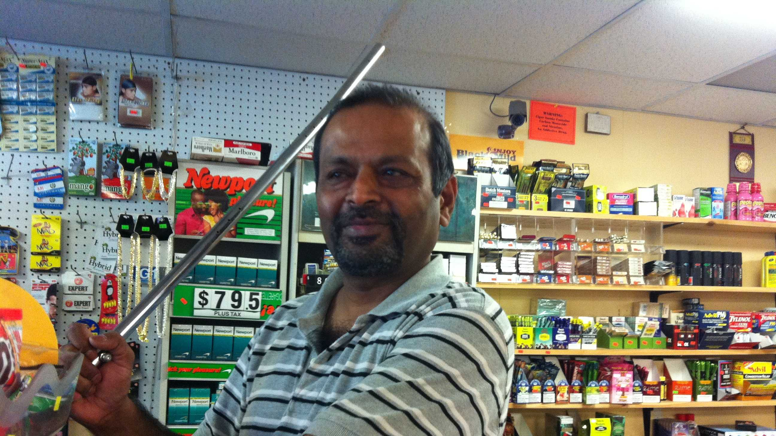 Nazir Shaikh holds the metal rod he hit one of the thieves with.