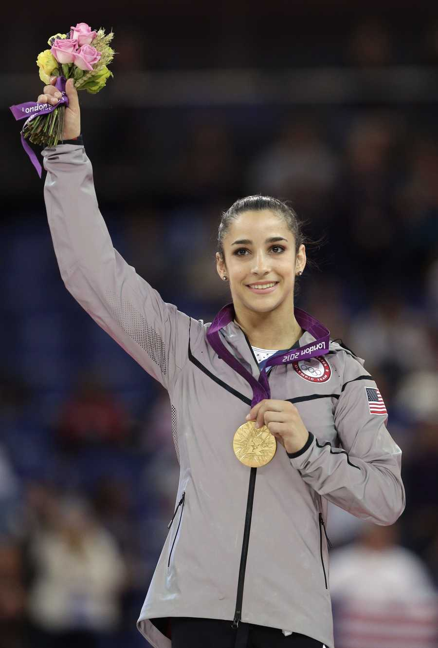 Alexandra Raisman displays her gold medal during the podium ceremony for the artistic gymnastics women's floor exercise final.