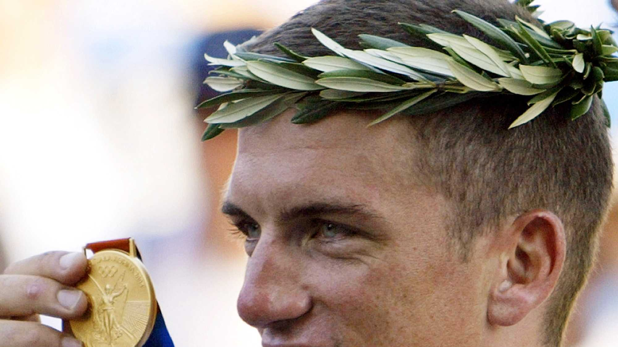 In this Aug. 18, 2004, photo, Tyler Hamilton holds up his gold medal after the men's road individual time trial of the 2004 Olympic Games in the outskirts of Athens.