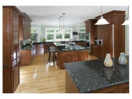 A spacious kitchen features custom flooring, granite countertops, and a walk-in storage area.