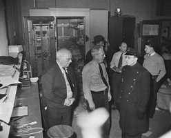 """Patrolman Thomas O'Brien (left fore ground) talks with Charles S. Grell (center) and Herman G. Pfaff (right), two of the five employees of Brink's Inc., who were tied up and gagged by bandits who fled with more that a million dollars from open vault (right, rear) in Boston, Massachusetts,, Jan. 17, 1950. Police said the robbers reached the second floor of the garage by opening six locked doors, """"probably with a passkey."""""""