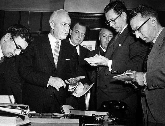 U.S. Attorney Anthony Julian tells newsmen in Boston, Jan. 12, 1956 of the arrest of six men charged with participating in the Brinks robbery. The arrests were made just five days before the statute of limitations was to run out.