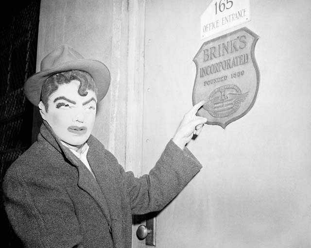 A newsman wears a rubber mask similar to that worn by seven bandits who robbed Brink's armored car firm in Boston of $1,500,000, Jan. 18, 1950. The reporter points to name plate on first of six locked doors opened by the gunmen. Mask was one of several purchased in joke shops by newsmen and police to see if they resembled description given by Brink's employees.