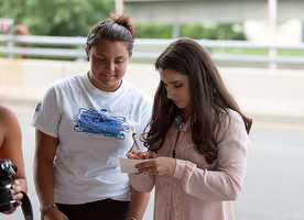 Raisman signs an autograph at Logan Airport for a fan.