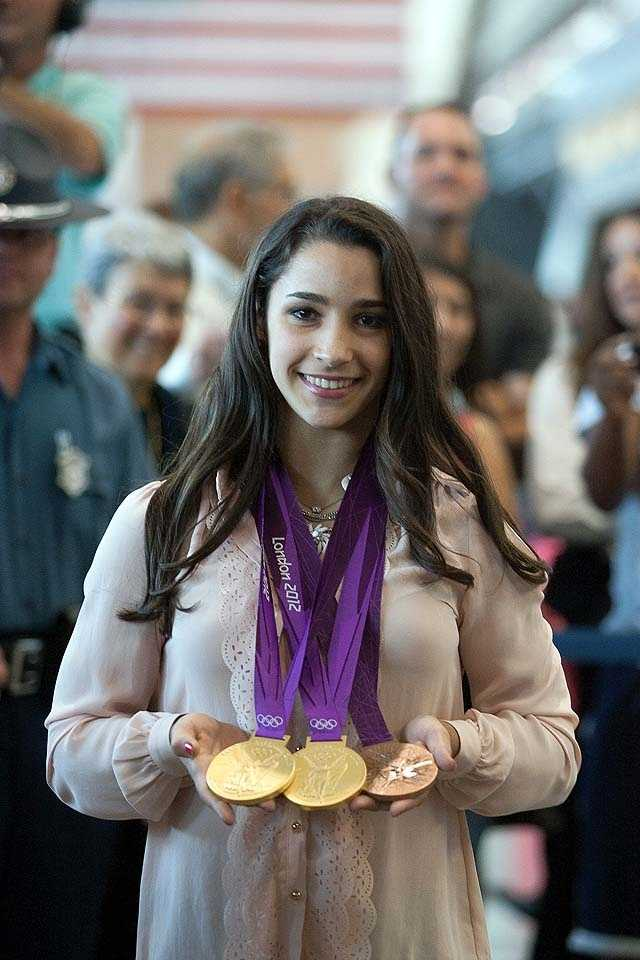 The Needham teenager returned to Massachusetts on Wednesday weighed down by the two gold and one bronze medal she won at the London games.