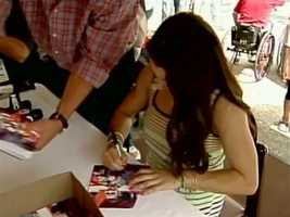 Aly signs pictures for fans