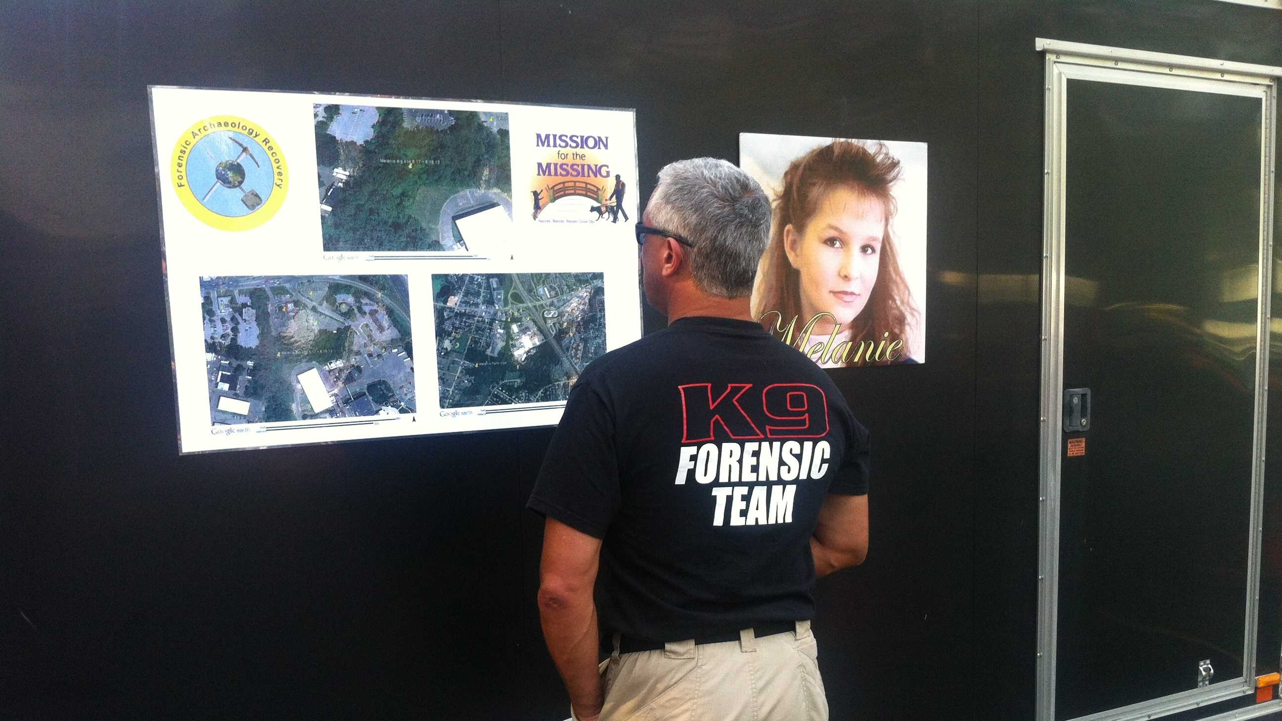 Search team member stand before photo of missing teen, Melanie Melanson.