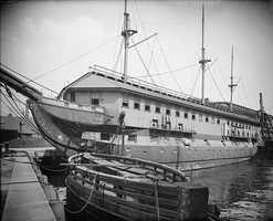 USS Constitution as a barracks ship ca. 1905 with the caisson gate for Dry Dock No. 1 at the Charlestown Navy yard floating in the foreground