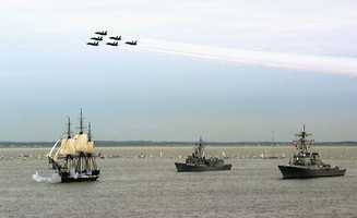 """USS Constitution fires her guns in salute while underway in Massachusetts Bay, escorted by the frigate USS Halyburton (FFG-40) (center) and the destroyer USS Ramage (DDG-61) (right), as the United States Navy's """"Blue Angels"""" pass overhead. Commissioned on 21 October 1797, Constitution set sail unassisted for the first time in 116 years onJuly 21, 1997."""