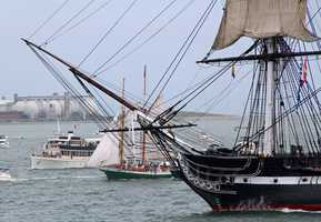 With Deer Island in the background, USS Constitution sails into the inner harbor as a sailboat passes along side.