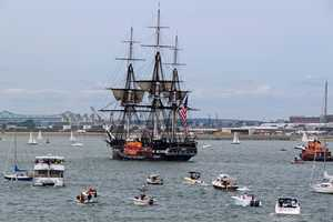 A flotilla of pleasure craft trails USS Constitution as the ship makes its way back in.