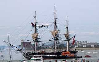 As the ship fires a 21-gun salute -- the smoke can be see at the bow --- a plane is on approach to Logan Airport.