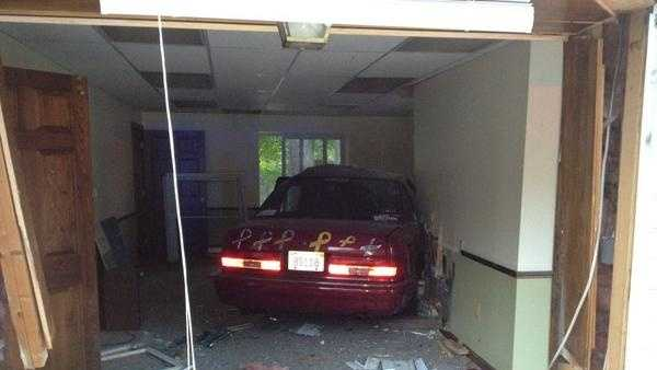 A two car crash lands an elderly driver and her car inside a Charlton home.