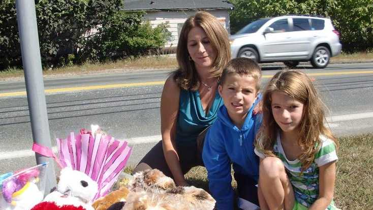 Allison Karsay, left, with her son, Michael, and daughter, Ava, both 6, at the roadside memorial on Central Street in Stoughton in memory of Shayla Lutz, three, killed when hit by a vehicle at that spot.