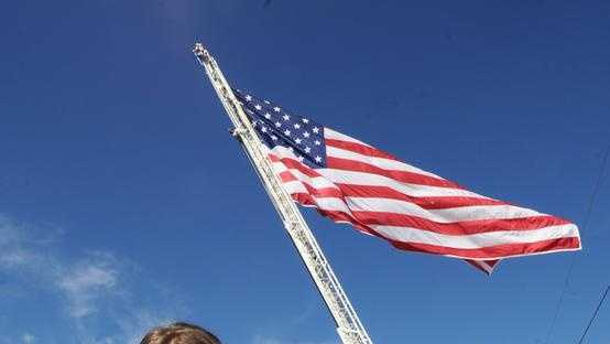 Isabella Iacobucci, 7, Stoughton, raised $2,400 to purchase a 30 x 50 Old Glory, which hangs above Stoughton Center from ladder truck 2 of the Stoughton Fire Department, on Tuesday, Sept. 11, 2012. She purchased the flag from a Massachusetts company.