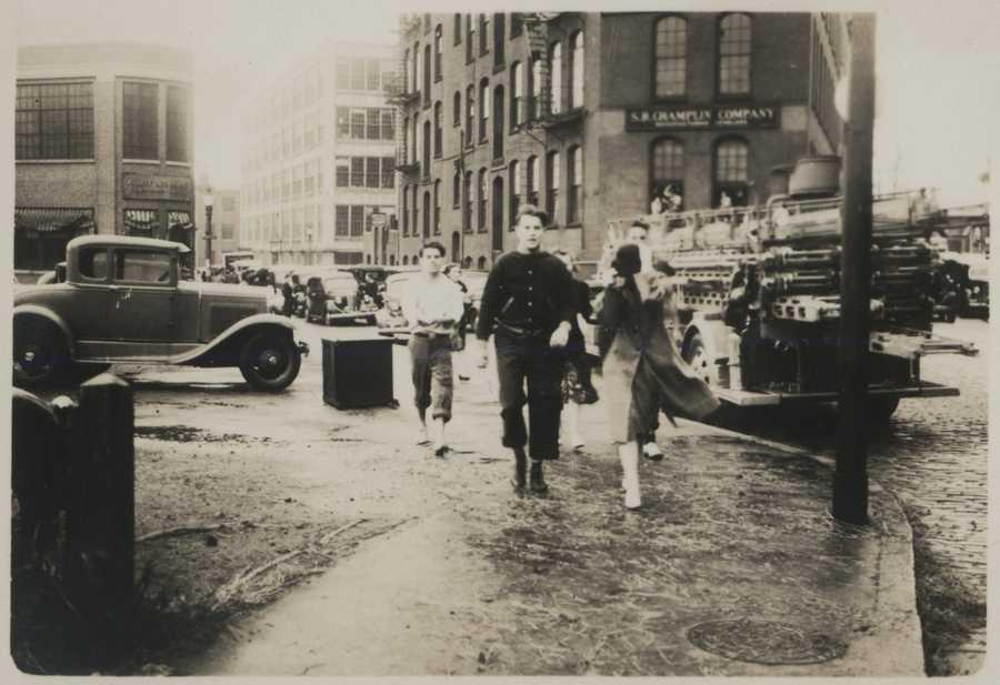 Walking down Ship Street in Providence after the waters receded. Men have their trousers rolled up to navigate areas of standing water. New England Hurricane of 1938.