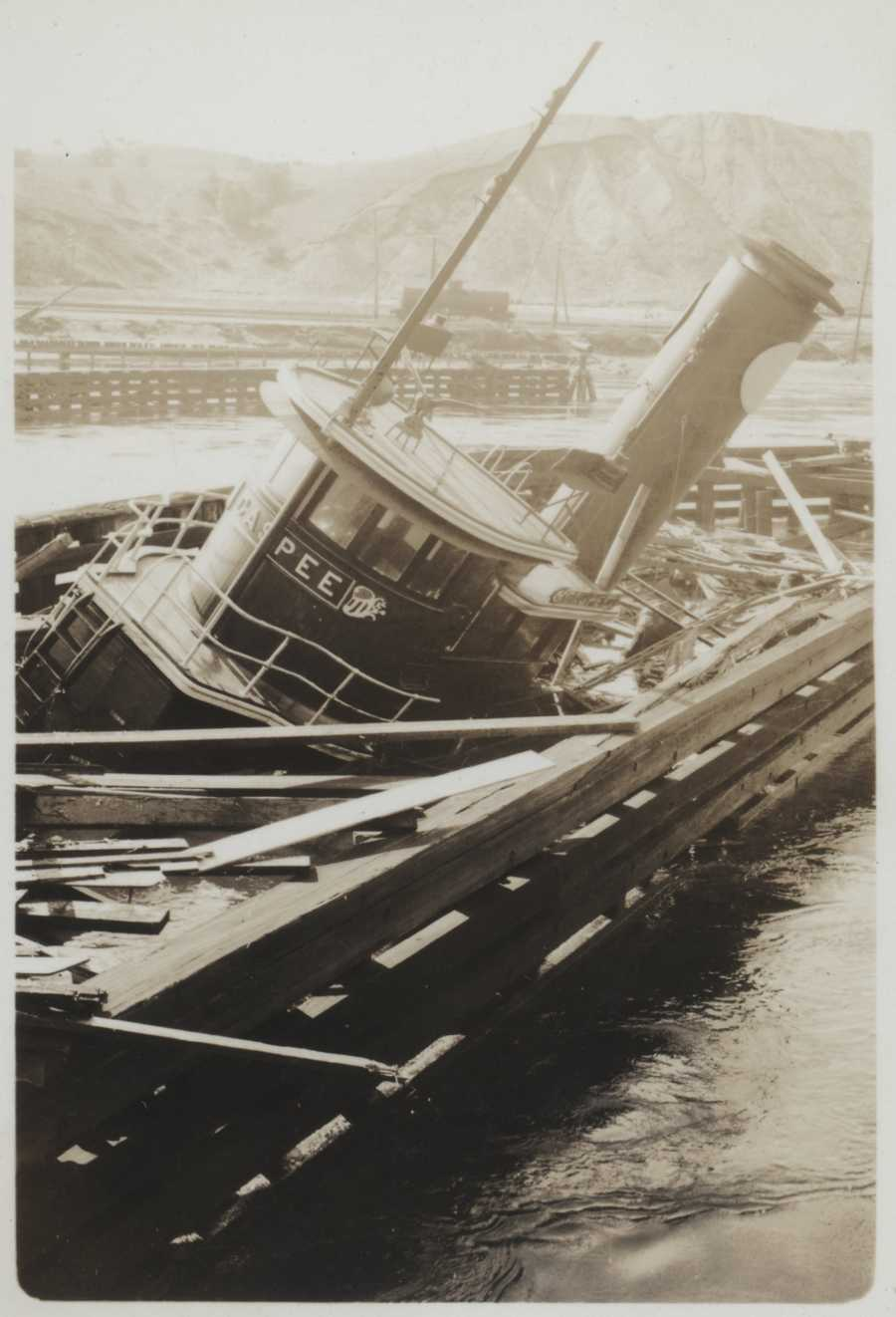 The tug Gaspee sitting on the bottom over a what appears to be the remains of a destroyed pier. New England Hurricane of 1938.
