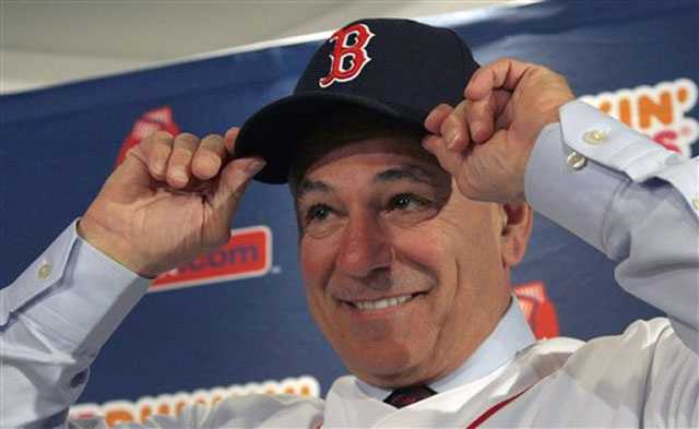 Boston Red Sox manager Bobby Valentine puts on a cap during a news conference at Fenway Park in Boston, Thursday Dec. 1, 2011. The 61-year-old former Rangers and Mets skipper and ESPN analyst was the 45th manager of the Boston Red Sox.
