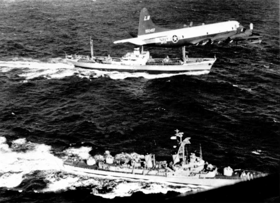 The U.S. destroyer Barry pulls alongside the Russian freighter Anosov in the Atlantic Ocean, November 10, 1962, to inspect cargo as a U.S. patrol plane flies overhead. The Soviet ship presumably carries a cargo of missiles being withdrawn from Cuba.