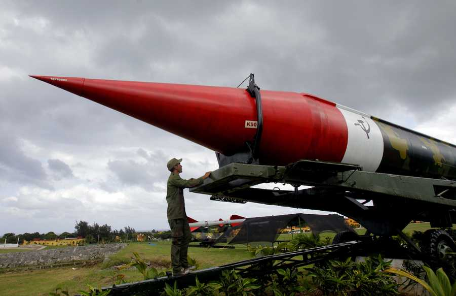 A soldier pauses to look at the outer casing of an old empty Soviet missile on exhibit as he works to paint it at the military complex Morro Cabana which is open to tourists in Havana, Cuba, Saturday, Oct. 13, 2012.