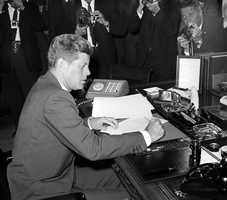President John F. Kennedy is surrounded by photographers, as he sits at his desk in the White House, in Washington, D.C., on October 23, 1962, shortly after signing a presidential proclamation concerning the Cuba crisis.
